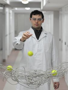 The viscosity does not depend only on the microscopic structure of a complex fluid (in the picture a cable coil represents polymer coils in a liquid), but also on the size of the probe used (represented by a tennis ball in the demonstration). The phenomenon is presented by Tomasz Kalwarczyk, a PhD student from the Institute of Physical Chemistry of the PAS. (Source: IPC PAS/Grzegorz Krzyżewski)