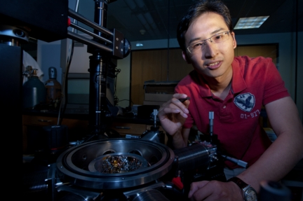 Rice University graduate student Jun Yao holds a memory chip made of silicon oxide. This chip will spent two years at the International Space Station as part of an experiment, HiMassSEE, to test it for susceptibility to radiation. (Credit Jeff Fitlow/Rice University)