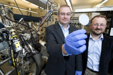 Purdue professors Michael Manfra, from left, and Gabor Csathy stand next to the high-mobility gallium-arsenide molecular beam epitaxy system at the Birck Nanotechnology Center. Manfra holds a gallium-arsenide wafer on which his research team grows ultrapure gallium arsenide semiconductor crystals to observe new electron ground states that could have applications in high-speed quantum computing. (Purdue University photo/Andrew Hancock)