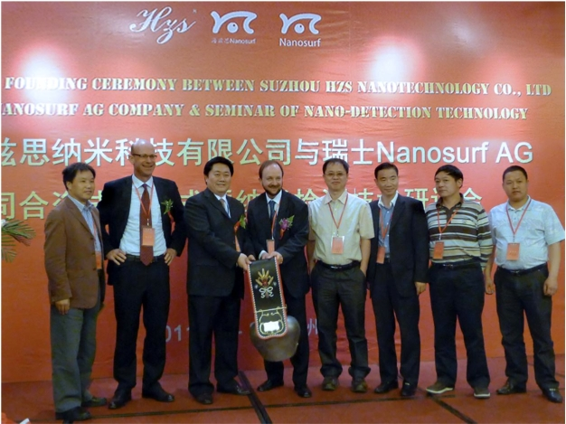 Dr. Urs Matter, CEO of Nanosurf (2nd on the left) and Dr. Lukas Howald, chairman of the board for Nanosurf (4th on the left) hand over a present of �Swiss culture� to Dr. Luo, CEO of Hzs (3rd on the left). Several representatives of China�s higher education institutions and members of the Chinese Ministry of Education took part in the celebration event at Suzhou Industrial Park.