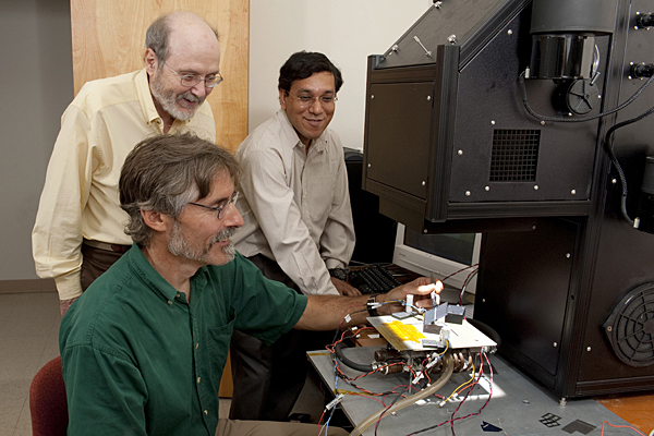 Steve Hegedus (seated), Robert Birkmire and Ujjwal Das at work at the University of Delaware's Institute of Energy Conversion. Hegedus will lead a $3.3 million project, along with Birkmire and Das, to lower the cost of crystalline silicon solar cells.