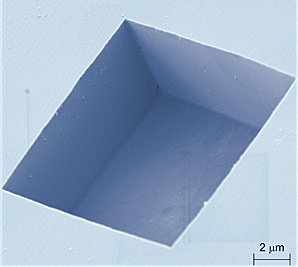 This colorized electron microscope image reveals the boxy shape of the pits the NIST team etched into the diamond surface, exhibiting their smooth vertical sidewalls and flat bottom. The pits were between 1 and 72 micrometers in size.