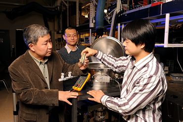 Xinwei Wang, Guoqing Liu and Xiaopeng Huang, left to right, show the instruments they used to study the thermal conductivity of spider silk.  Photo by Bob Elbert.