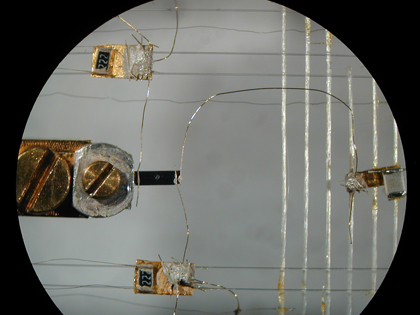 "This microscope image shows thermometers (top and bottom) and a heater (right) connected via 50-micrometer-wide gold wires to a black rectangle of the ytterbium dirhodium disilicide (center) that is only three-quarters of a millimeter wide. Using this setup, researchers at the Max Planck Institute for Chemical Physics of Solids in Dresden, Germany, induced a thermal current by setting up a small difference in temperature at the two ends of the sample. The proportionality coefficient between this temperature difference and the thermal power provided by the heater defined the thermal conductivity of the sample, which was found to violate traditional laws of physics when the material was cooled to a ""quantum critical point.""