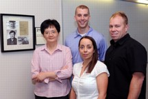 Members of Kan Wang's research team gather in a Hach Hall meeting area dedicated to the late Victor Lin of Iowa State University and the Ames Laboratory. From left to right are Wang, a professor of agronomy; Justin Valenstein, a doctoral student in chemistry; Susana Martin-Ortigosa, a post-doctoral research associate in Wang's lab; and Brian Trewyn, an associate scientist in chemistry.  Photo by Bob Elbert.