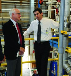 Forest Product Lab chemical engineer Rick Reiner (right) shows Under Secretary Sherman the new nanocellulose pilot plant.