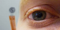 Figure 1: The contact lens display with the dollar sign held next to a human eye