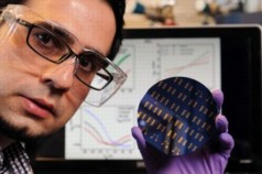 Georgia Tech postdoctoral fellow Hossein Sojoudi holds a wafer containing graphene p-n junctions, while the screen display in the background shows electrical data measured in the devices. (Credit: Gary Meek)