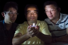 The University of Georgia's Zhengwei Pan, center, an associate professor of physics and engineering, holds a prototype of what is thought to be the world's first single-phosphor, single-emitting-center-converted LED that emits a warm white light while the UGA College of Engineering's Feng Liu, left, and Xufan Li look on.