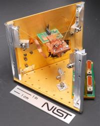 NIST's prototype solid-state refrigerator uses quantum physics in the square chip mounted on the green circuit board to cool the much larger copper platform (in the middle of the photo) below standard cryogenic temperatures. Other objects can also be attached to the platform for cooling.