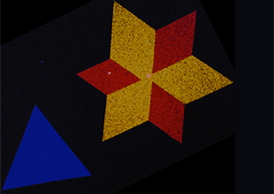 A false-color electron microscopy image showing the star-shaped crystals in monolayers of two-dimensional semiconducting molybdenum disulfide. The red, yellow, and blue colors represent two dominant crystal orientations that are stitched together by a line of atomic defects. Image courtesy of Pinshane Y. Huang and David A. Muller