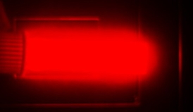 Bright light emission from silicon quantum dots in a cuvette. The image is from a camera that captures the near-infrared light that the quantum dots emit. The light emission shown is a psuedo color, as near-infrared light does not fall in the visible spectrum. Credit: Folarin Erogbogbo