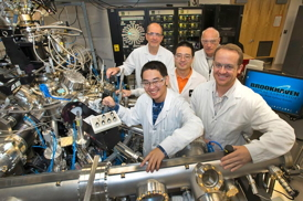 Click on the image to download a high-resolution version. Collaborating scientists stand with the atomic layer-by-layer molecular beam epitaxy system (ALL-MBE) used to synthesize the more than 800 differently doped samples used in the new study. Front row, from left: Yujie Sun, Anthony Bollinger; center: Jie Wu; back, from left: Ivan Bozovic, Zoran Radovic (visiting scientist from Serbia's Belgrade University).