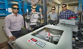 Click on the image to download a high-resolution version. Nanditha Dissanayake, Matthew Eisaman, Yutong Pang, and Ahsan Ashraf display the setup used to track the flow of electrons through the photoactive layer of organic solar cells. The red and black wires in the box in the foreground (also shown in close-up) are connected to a solar cell that is in contact with a prism. The prism guides laser light through the cell in a range of specific directions to gain precise information about how electrons flow.