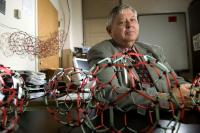 "Harry Dorn, a professor at the Virginia Tech Carilion Research Institute, poses with models of ""buckyballs."" His research supports the theory that a soccer ball-shaped nanoparticle commonly called a buckyball is the result of a breakdown of larger structures rather than being built atom-by-atom from the ground up.