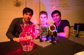 "MIT students (left to right) Ayush Bhandari, Refael Whyte and Achuta Kadambi pose next to their ""nano-camera"" that can capture translucent objects, such as a glass vase, in 3-D.