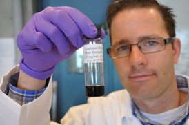 Jacob D. Lanphere, a Ph.D. student at UC Riverside, holds a sample of graphene oxide.