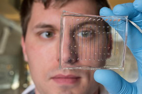 James Dahlman, an assistant professor in the Wallace H. Coulter Department of Biomedical Engineering at Georgia Tech and Emory University, holds a microfluidic chip used to fabricate nanoparticles that could be used to deliver therapeutic genes.