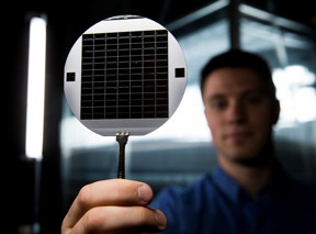 A graduate student at BYU holds up a disc of microchips that have flexible glass membranes.