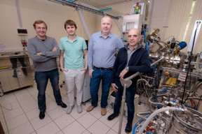 (From left) Dmitry Kuzmichev, Konstantin Egorov, Andrey Markeev, and Yury Lebedinskiy posing next to the atomic layer deposition apparatus at the Center of Shared Research Facilities, MIPT