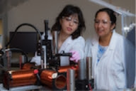 Rice University graduate student Elaa Hilou (left) and Professor Sibani Lisa Biswal set up an experiment in a device that combines a rotating magnetic field and a microscope. The researchers are studying the effects of a spinning field on magnetic particles. Their findings could help researchers model colloids for cosmetics as well as catalysts for chemicals, among other applications, in a physical system. (Credit: Jeff Fitlow/Rice University)