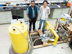 "Vikram Deshpande, assistant professor in the Department of Physics & Astronomy (left) and doctoral candidate Su Kong Chong (right) stand in the ""coolest lab on campus."" Deshpande leads a lab that can cool topological materials down to just a few fractions of a degree above absolute zero at -273.15°C (-459.67°F). It is literally the coldest laboratory on campus.