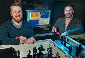 Postdoctoral fellow Erik Busby and Matt Sfeir with optical equipment they used to study charge carrier production in organic photovoltaic polymers at Brookhaven Lab's Center for Functional Nanomaterials.
