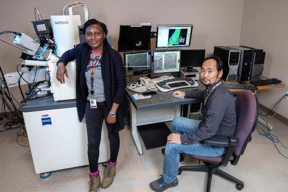 Abiola Temidayo Oloye, left, a fifth-year doctoral candidate and the lead author of a study published in Superconductor Science and Technology, at an electron microscope with Fumitake Kametani, an associate professor of mechanical engineering and principal investigator for the study at the FAMU-FSU College of Engineering.  CREDIT Mark Wallheiser/FAMU-FSU College of Engineering